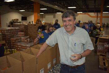 shippers group executive team member hugh tait smiles and packs commodity boxes at north texas food bank