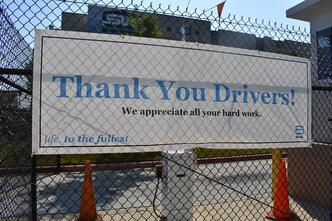 "large white and blue banner hanging on entry fence reading ""Thank you Drivers! Life, to the fullest"""