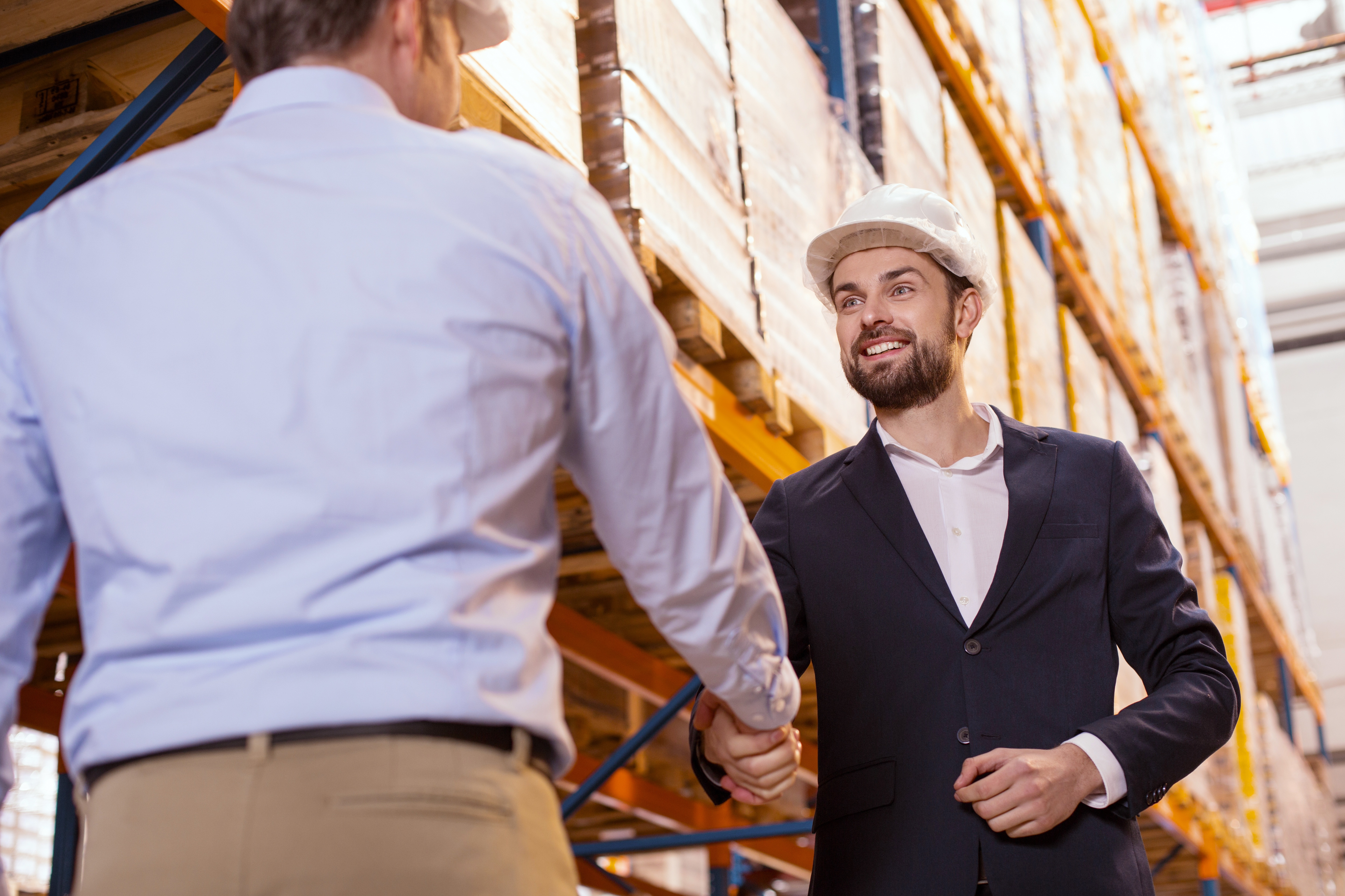 Two businessmen in hard hats standing in warehouse, smiling and shaking hands